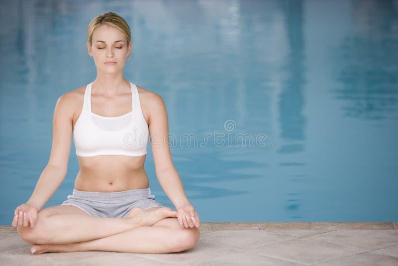 göra sittande kvinnayoga för poolside arkivfoto