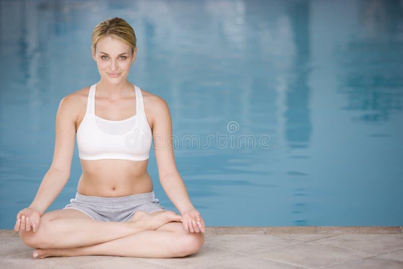 göra sittande kvinnayoga för poolside arkivbild