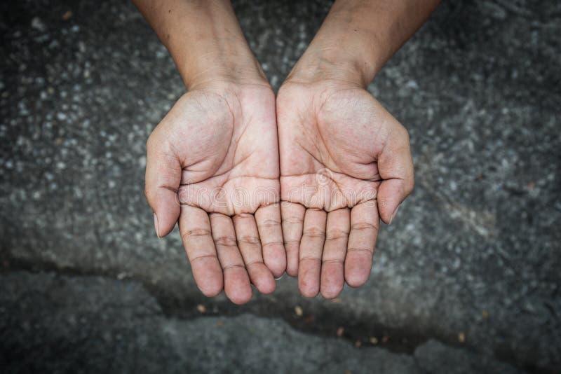 Göra till tiggare folk- och människaarmodbegreppet - personhänder som tigger f royaltyfri foto