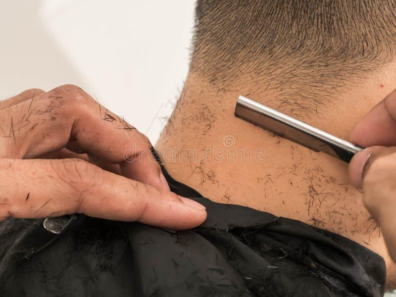 Göra upp stilfull frisyr på salongslutet barberare som rakar honom med rakkniven Skönhet modern stil, livsstil, trendbegrepp royaltyfri bild