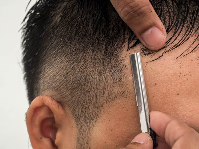 Göra upp stilfull frisyr på salongslutet barberare som rakar honom med rakkniven Skönhet modern stil, livsstil, trendbegrepp royaltyfri fotografi