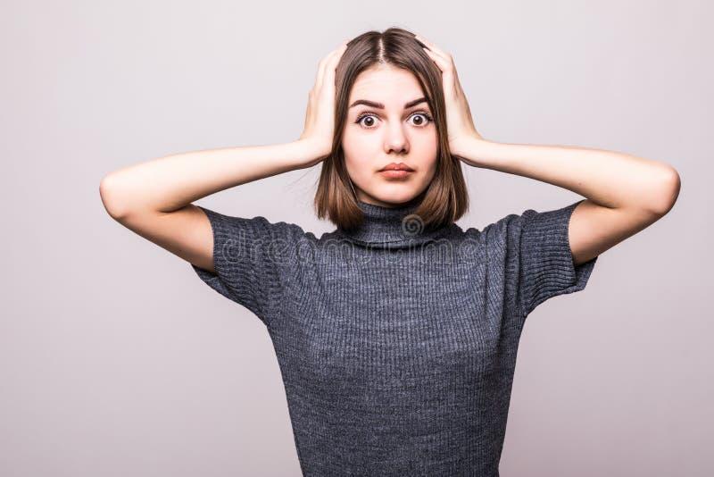 göra wrong Uppriven kvinna för stående som smäller handen på huvudet som har duh ögonblick på grå bakgrund arkivfoton