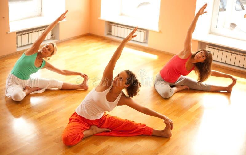 Göra yoga i hälsoklubba arkivbild