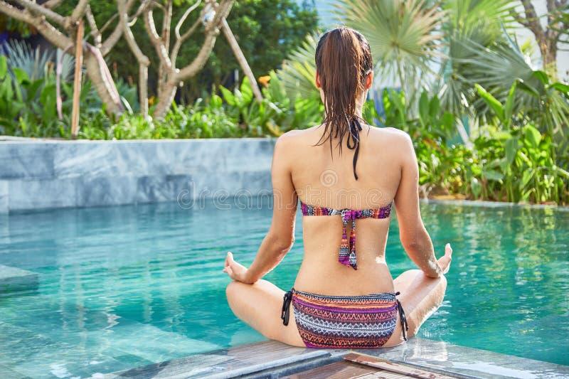 Göra yoga vid pölen fotografering för bildbyråer