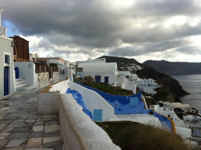 Görande mörkare himlar ovanför den Oia gatan och hus på lutningen landskap i Santorini i Grekland arkivfoto