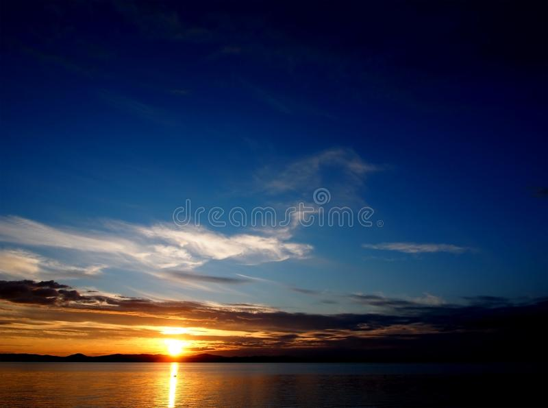 Görande mörkare solnedgånghimmel över sjön med färgrika moln, guld- timme royaltyfria bilder