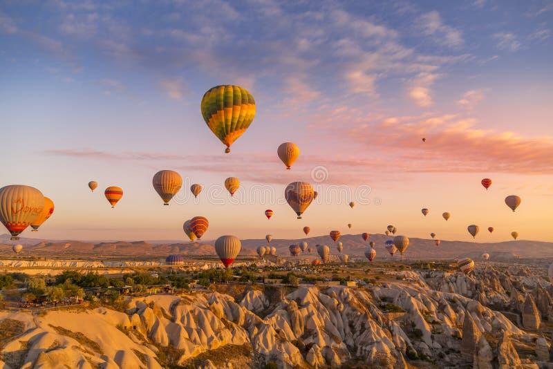 Göreme, Cappadocia, Turquia - 7 de outubro de 2019: Balões de ar quente cheios de turistas no nascer do sol flutuando ao longo do imagem de stock