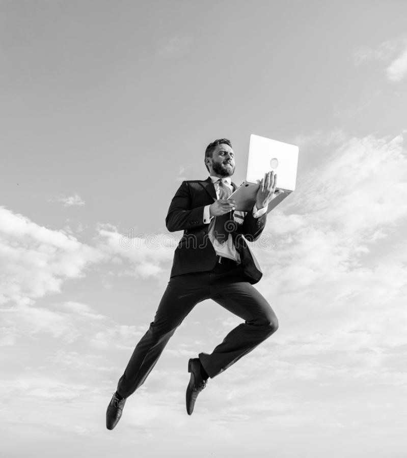 Göttlicher Manager Geschäftsmanngesellschaftsanzugfliege in einer Luft mit Hintergrund des blauen Himmels des Laptops Wunderbar o stockfoto