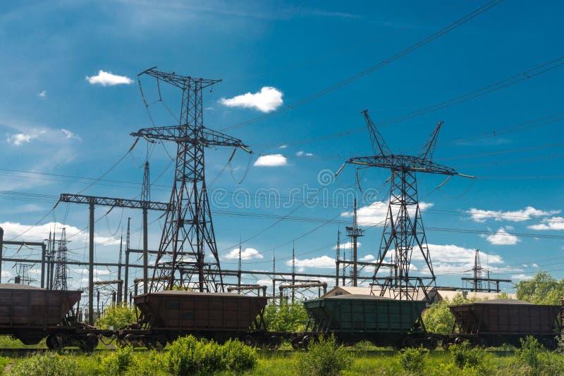 Güterzug überschreitet durch Wärmekraftwerke und Stromleitungen Elektrische Nebenstelle der Verteilung lizenzfreies stockfoto