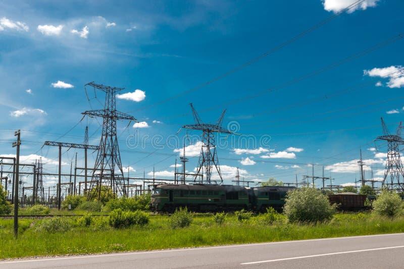 Güterzug überschreitet durch Wärmekraftwerke und Stromleitungen Elektrische Nebenstelle der Verteilung lizenzfreie stockbilder