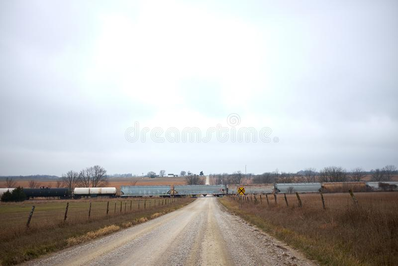 Güterzug, der einen ländlichen Schotterweg kreuzt lizenzfreie stockbilder