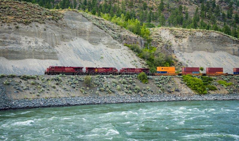 Güterzug der kanadischen pazifischen Eisenbahn, die entlang Thompson River sich bewegt lizenzfreie stockfotos
