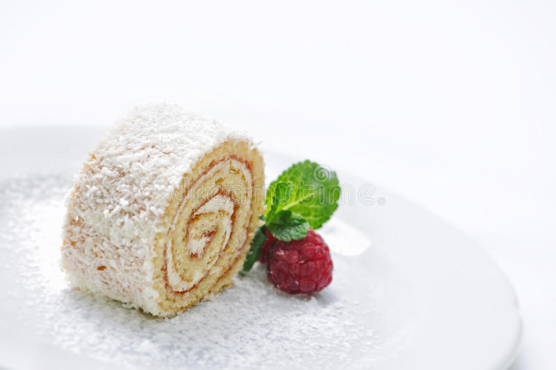 Gąbki rolki tort z kremową i owocową dekoracją na bielu talerzu, linii sklepowa fotografia, patisserie, słodki deser fotografia royalty free