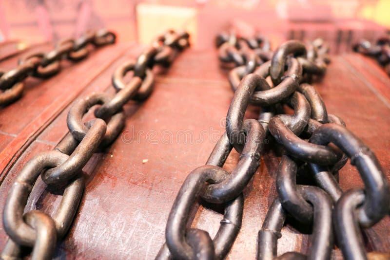 Gęści, silni, żelazni, stalowi starzy łańcuchy przeciw tłu antyczny drewniany, zdjęcia stock