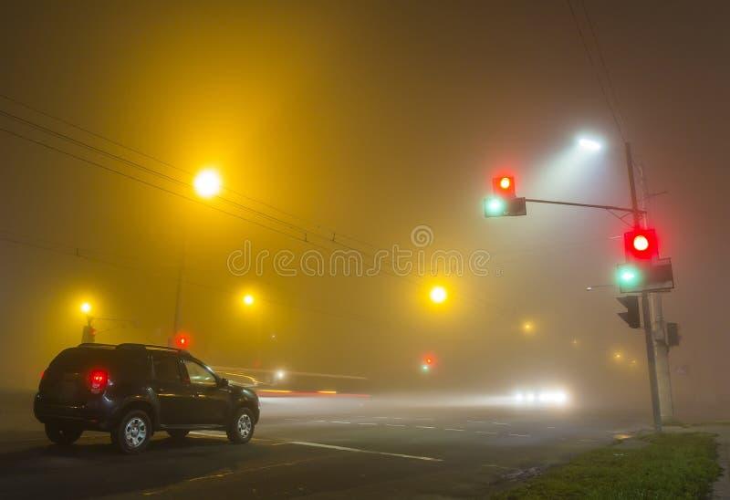 Gęsta mgła nad pustą drogą z osamotnionym samochodem i światłami ruchu przy fotografia stock