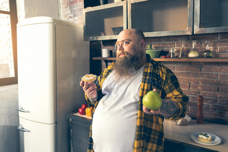 Gęsty facet robi wyborowi między zdrowym i niezdrowym jedzeniem fotografia stock