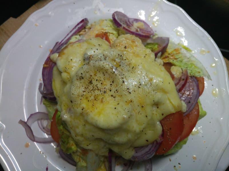 Gęsty rozciekły ser na hamburgerze na białym talerzu zdjęcia stock