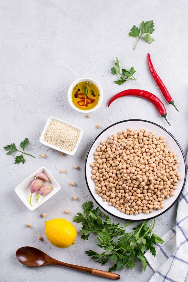 Główni składniki dla robić hummus, chickpea, cytryna, czosnek, sezam, olej, pieprz, pietruszka odgórny widok knedle tła jedzenie  zdjęcie royalty free