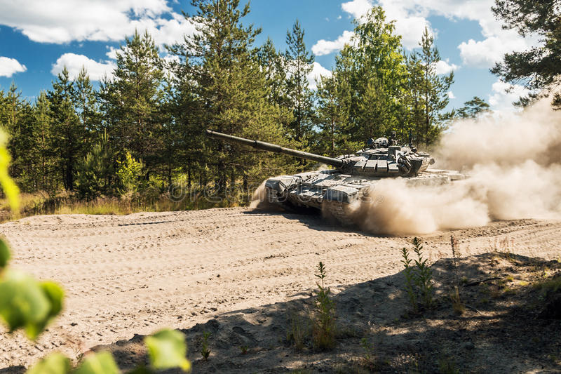 Główny Batalistyczny zbiornik Rosja iść odkurzać na lasowej drodze obrazy stock