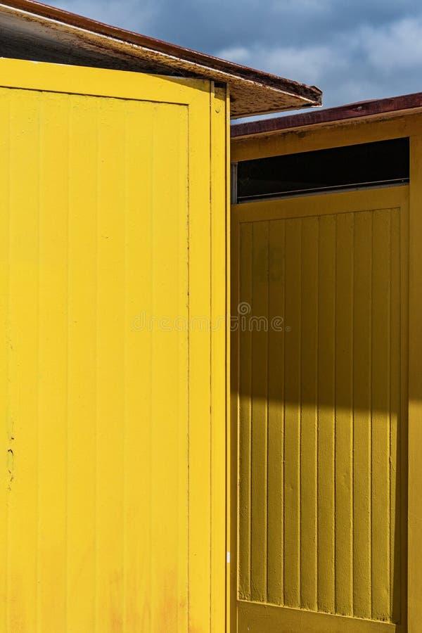 Głęboki - kolor żółty malował plażowe budy na pogodnym ale markotnym dniu, Niebieskie niebo, białe chmury, nadmorski wakacje arch zdjęcie stock