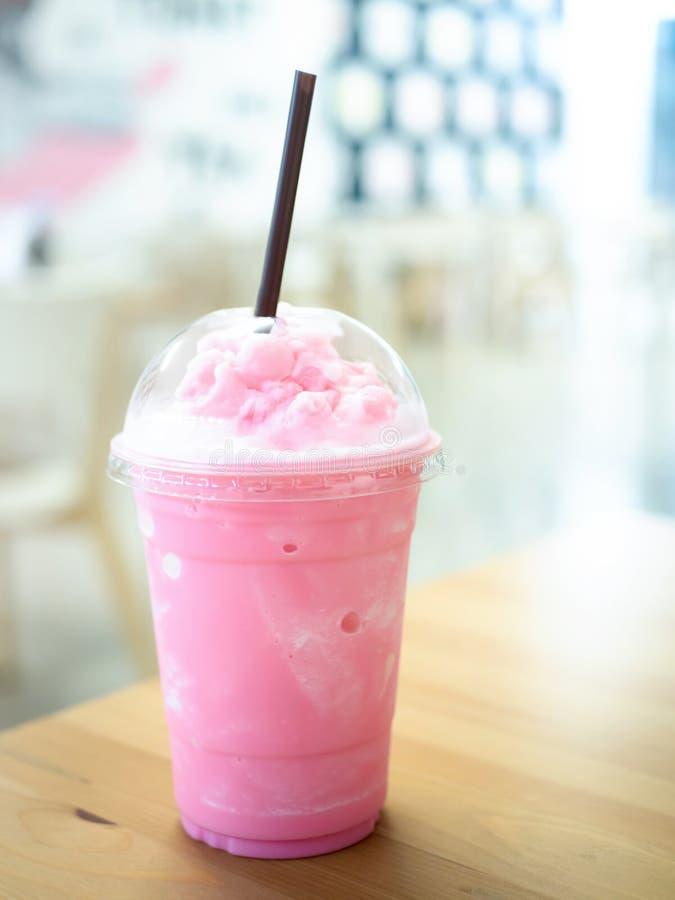 Gładkość z zimnego mleka w plastikowej kubce na drewnianym stole i ma piękne tło w słońcu obrazy stock