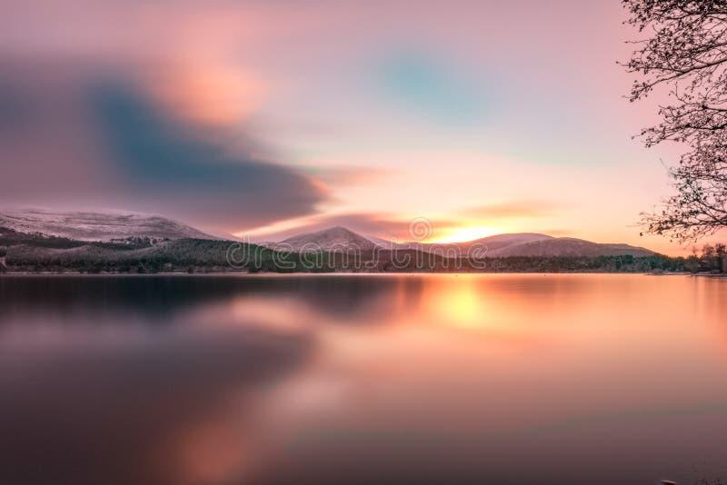 Gładzi długiego ujawnienie zimy wschód słońca z pomarańczowego koloru żółtego słońca cieniami i odbiciem zdjęcia stock