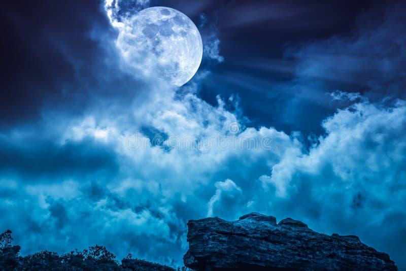 Głaz przeciw niebieskiemu niebu z chmurami i pięknym księżyc w pełni przy zdjęcie stock