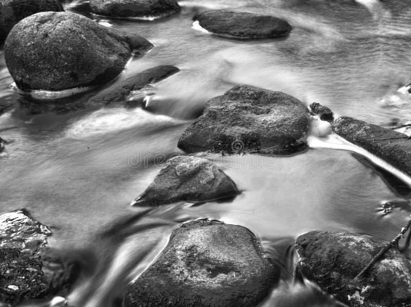 Głazy i skały w strumieniu, czarny i biały Żołnierza piechoty morskiej i oceanu temat zdjęcie royalty free