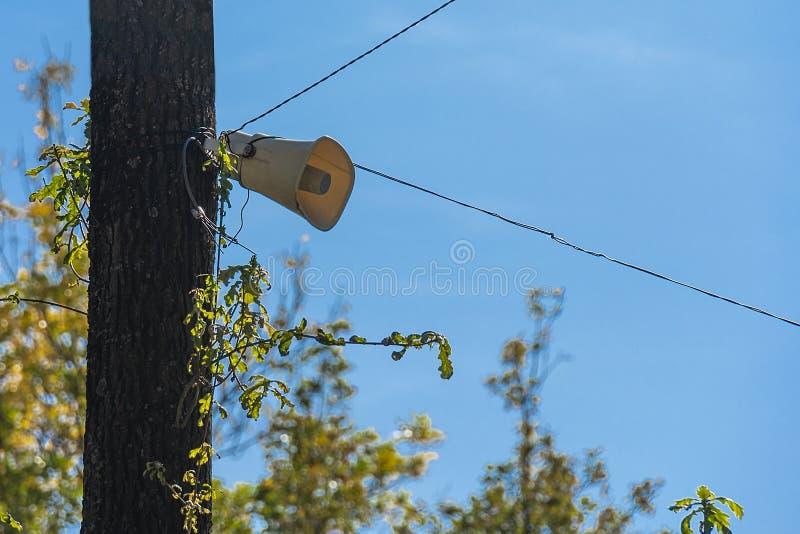 Głośnik na drzewie na niebieskim niebie w parku Transmisja na głos w miejscach publicznych Alert fotografia stock