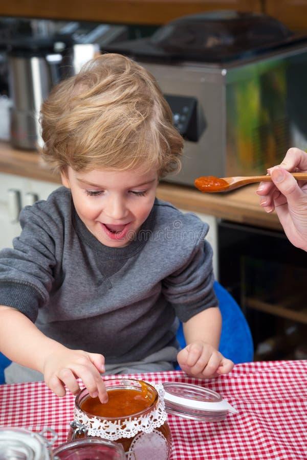 Głodna chłopiec zamacza palec w słoju dżem zdjęcia stock