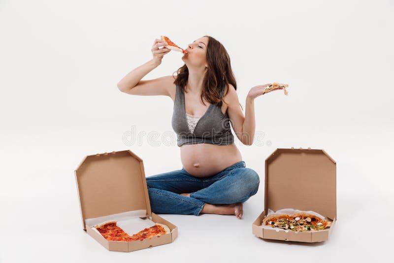 Głodna kobieta w ciąży łasowania pizza obraz stock