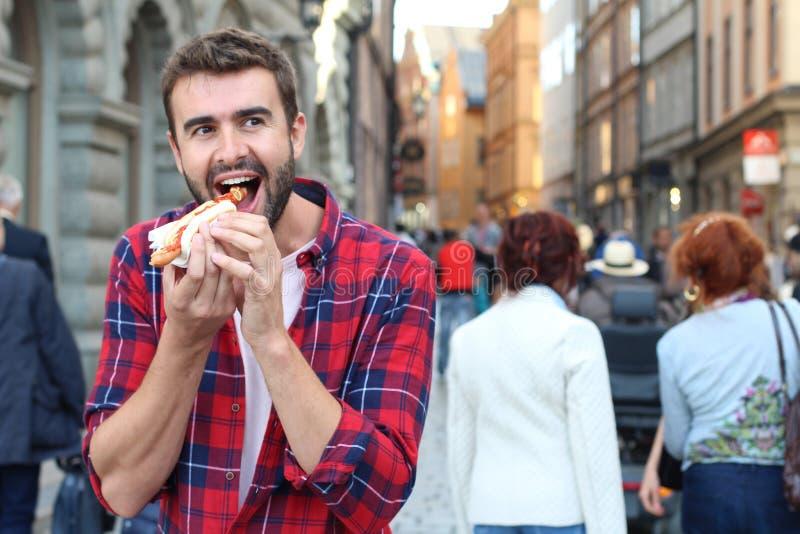 Głodna samiec pożera hot dog obraz stock