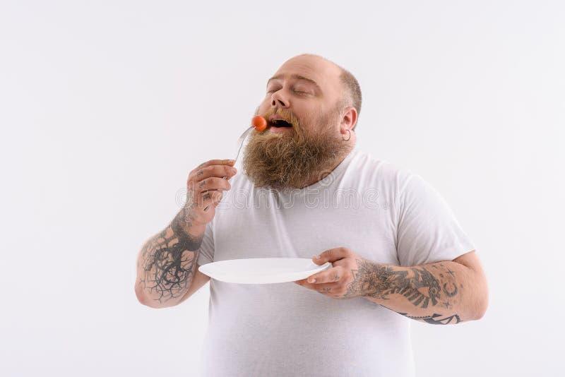 Głodny gęsty facet je malutkiego warzywa obrazy royalty free