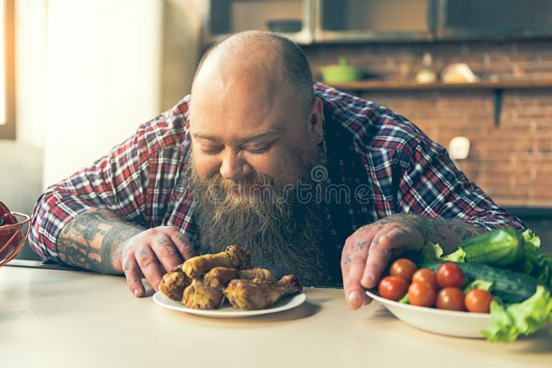 Głodny gęsty facet wącha mięso z przyjemnością zdjęcia royalty free