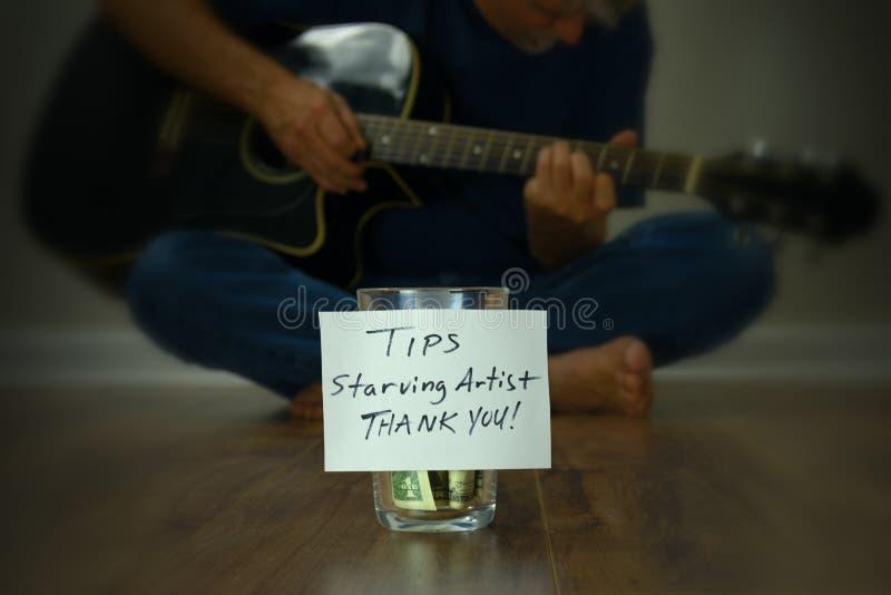 Głodującego artysty gitarzysty uliczny wykonawca z porady filiżanki słojem obrazy royalty free