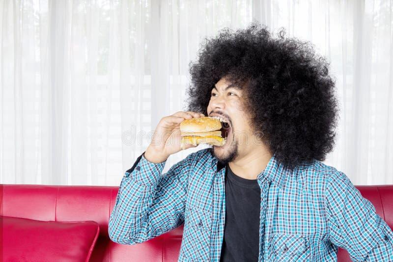 Głodujący młodego człowieka łasowania cheeseburger w domu fotografia stock