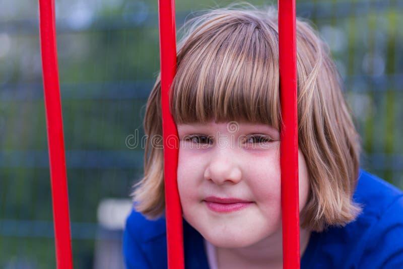 Głowa młoda dziewczyna za czerwonymi metali barami zdjęcie stock