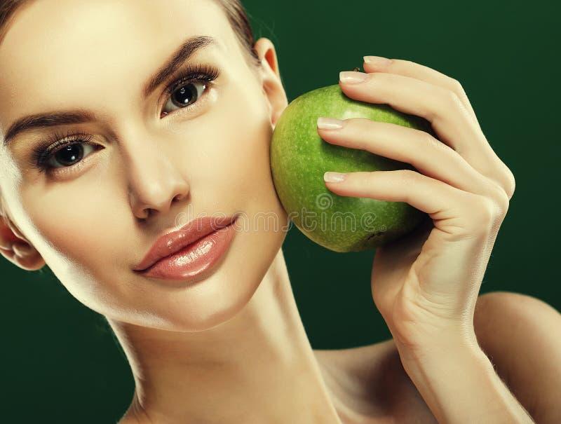 Głowa strzał kobiety mienia zieleni jabłko przeciw zielonemu tłu fotografia stock