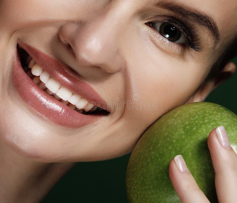 Głowa strzał kobiety mienia zieleni jabłko przeciw zielonemu tłu zdjęcia stock