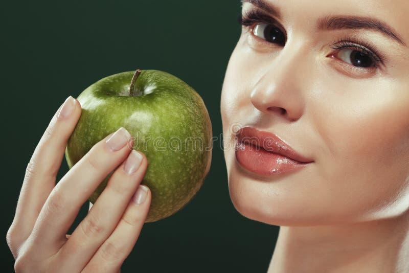 Głowa strzał kobiety mienia zieleni jabłko przeciw zielonemu tłu zdjęcia royalty free