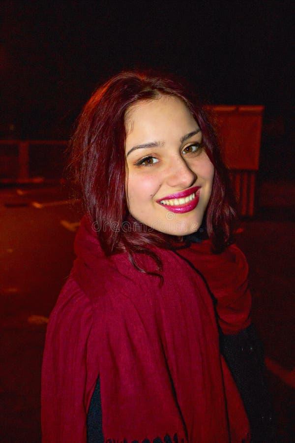 Głowa strzał Piękna czerwieni głowy dziewczyna z czerwonym szalikiem na zimnej zimy nocy i z perfect uśmiechem, ładnymi oczami i  obrazy stock