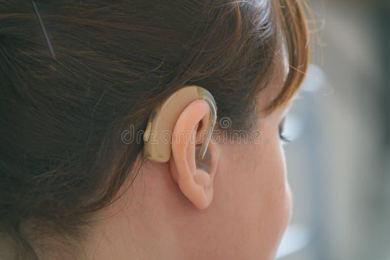 Głucha kobieta nosząca aparat słuchowy zdjęcia stock