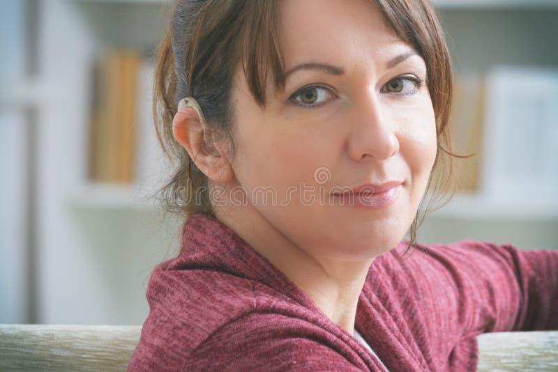 Głucha kobieta nosząca aparat słuchowy zdjęcie stock