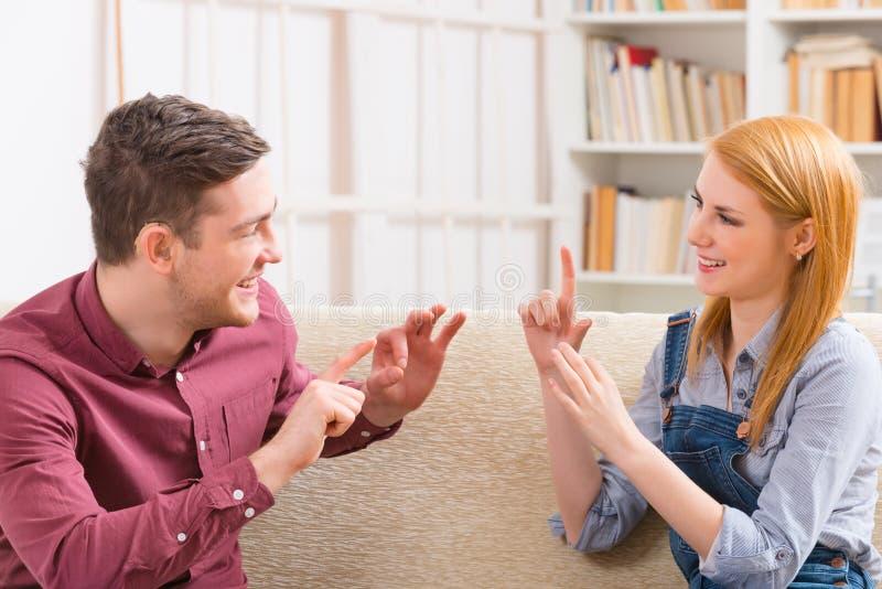 Głuchy mężczyzna z jego dziewczyną używa szyldowego języka zdjęcie royalty free