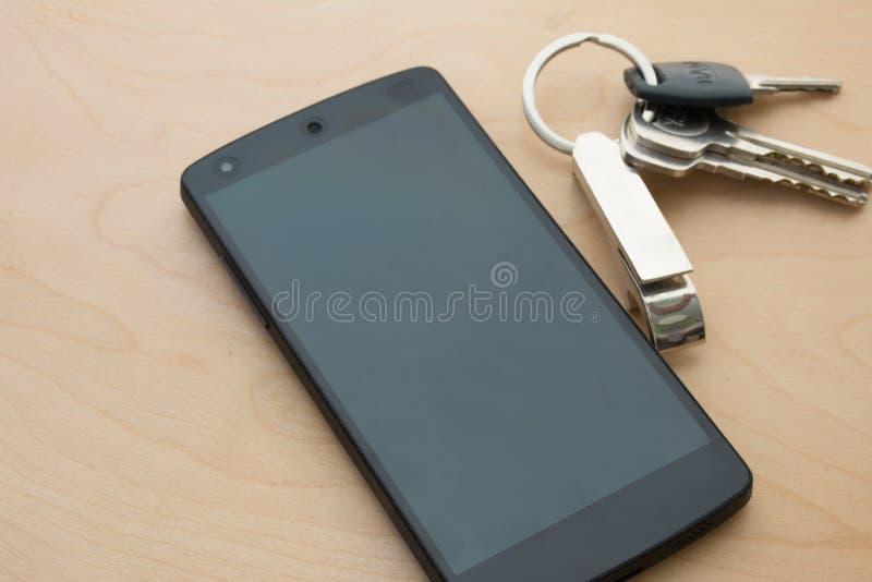 4G智能手机wite在木地板上的房子钥匙 免版税库存图片