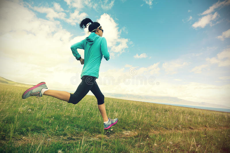 G fitness woman runner running on beautiful trail in grassland. Healthy lifestyle young fitness woman runner running on beautiful trail in grassland stock image