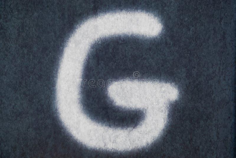 G isolerad kritabokstav i svart tavlabakgrund arkivfoton