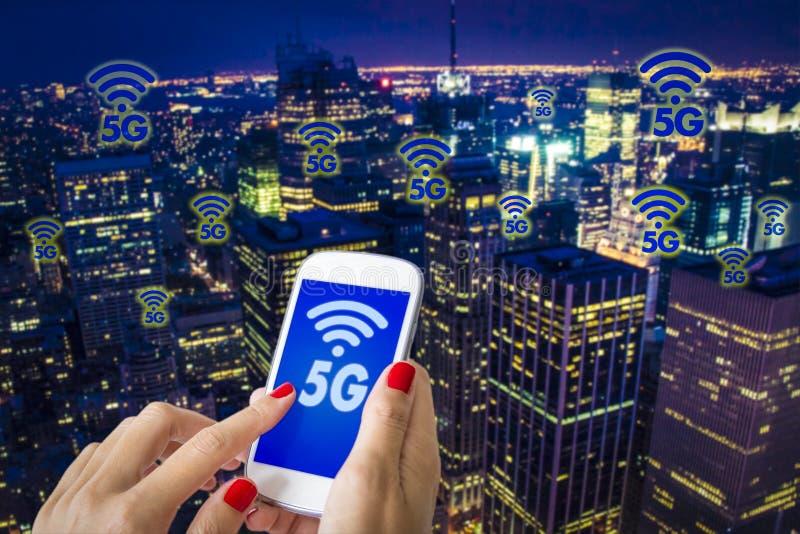 5G of LTE-presentatie Vrouwenhand die smartphone met moderne stad op de achtergrond gebruiken stock fotografie