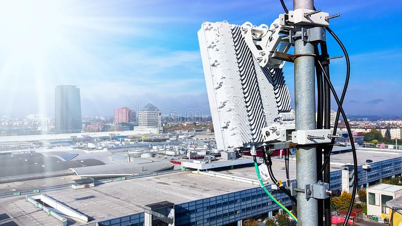 5G mobile telecommunication cellular radio network antenna. S on a mast on the roof broadcasting signal waves over the city on a clear sunny day with blue sky stock image