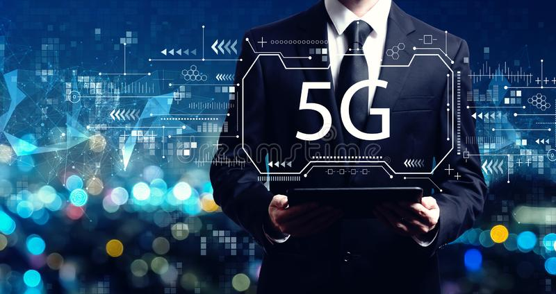 5G network with businessman holding a tablet stock photos